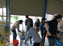 Students use a shovel and their hands to mix concrete powder into a mixture of sand and gravel.