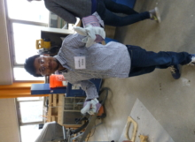 A student poses with his gloves prior to mixing up the concrete.