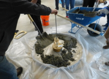 Students pour concrete into the round sanitation slab mold.