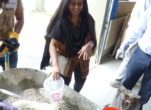 Students add a pre-determined amount of sand and gravel to the wheelbarrow to create the concrete mix.
