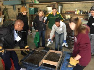 Students fill a sieve with sands and small rocks to separate the particulates for the filter concrete mixture.