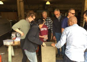 Students inspect the finished concrete biosand water filter after taking it out of the mold.